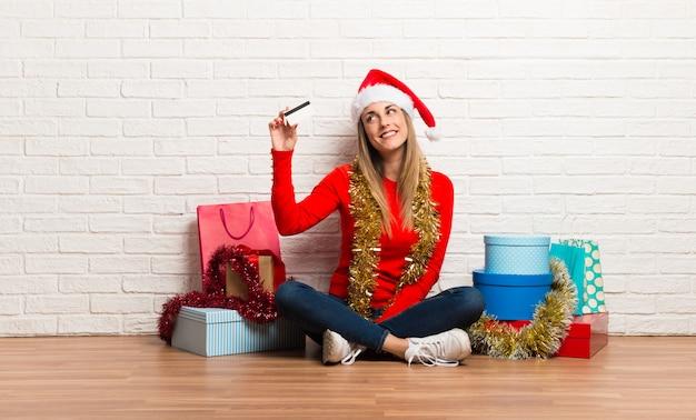 Menina, com, chapéu natal, e, muitos, presentes, celebrando, a, natal, feriados, segurando, um, cartão crédito