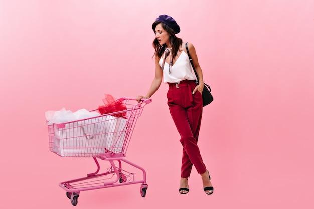 Menina com chapéu olha para o carrinho e lembra se comprou tudo na loja. senhora de calças clássicas com uma bolsa preta posa para a câmera.