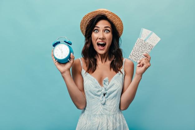 Menina com chapéu parece engraçado para a câmera e guarda despertador, ingressos em fundo azul