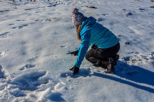 Menina com chapéu pegando neve do chão na montanha.