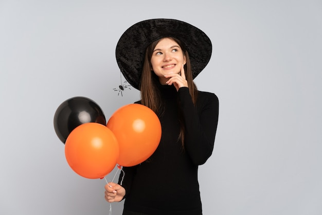 Menina com chapéu preto e vestido preto segurando balões