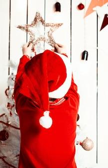 Menina com chapéu vermelho colocando uma estrela no topo da árvore de natal em um quarto decorado