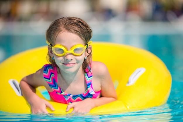Menina com círculo de borracha inflável na piscina