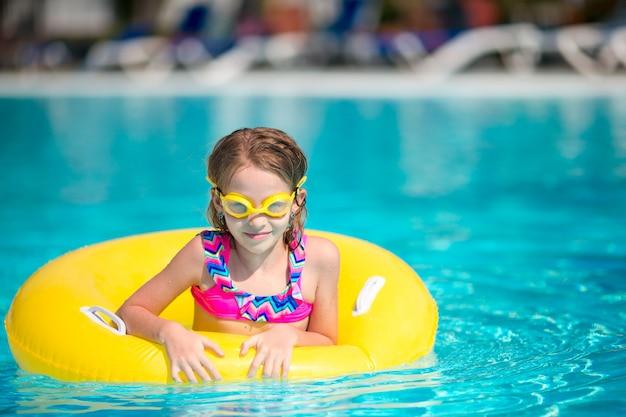 Menina com círculo de borracha inflável se divertindo na piscina
