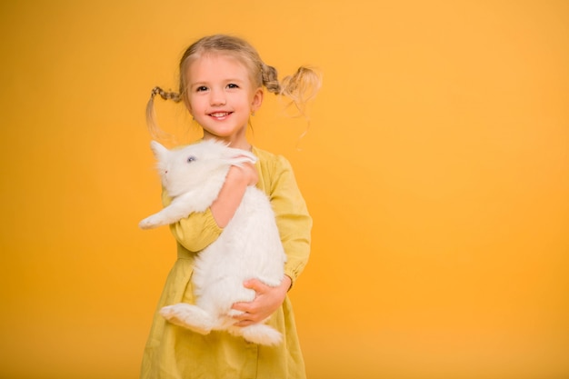 Menina com coelhinho da páscoa em fundo amarelo