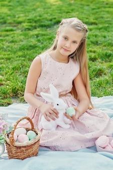 Menina com coelho e ovos para a páscoa no parque na grama verde