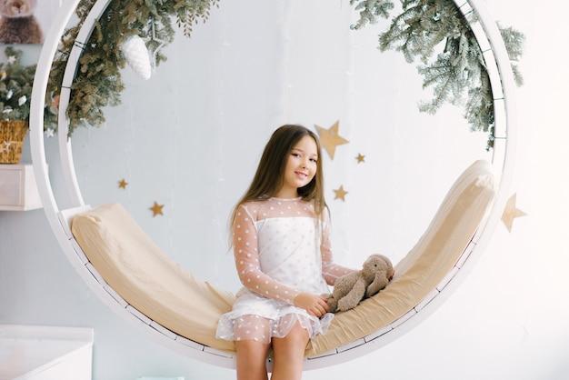 Menina com coelho em um balanço de natal no quarto das crianças