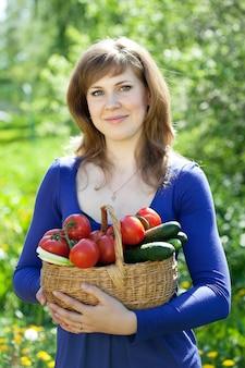Menina com colheita de legumes