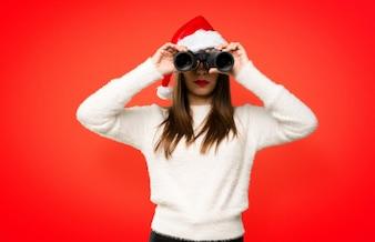 Menina com comemorando as férias de Natal e procurando algo à distância