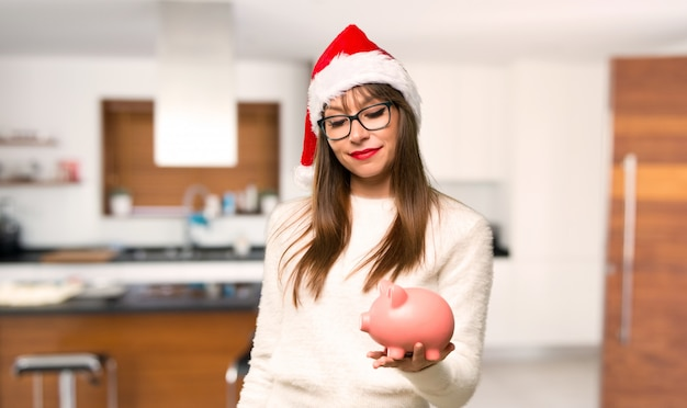 Menina com comemorando as férias de natal tomando um cofrinho e feliz porque é f