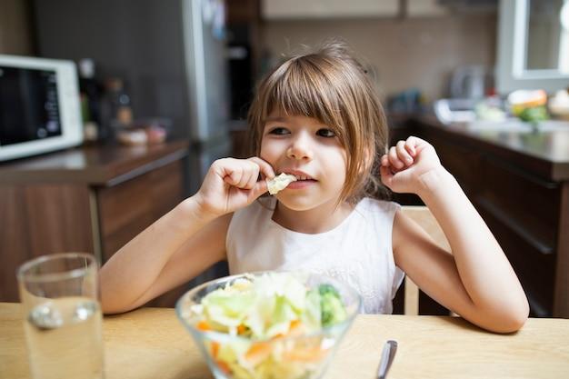 Menina com comida saudável em casa