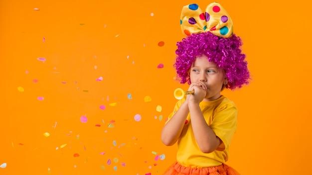 Menina com confete e fantasia de palhaço