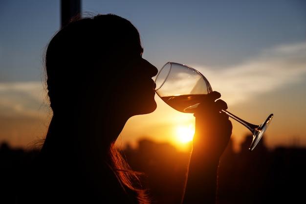 Menina com copo de vinho. silhueta negra.