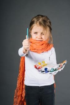 Menina com cores de água e pincel nas mãos