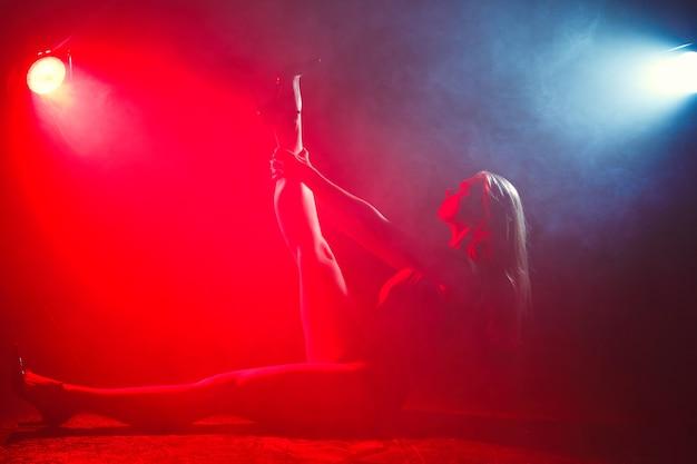 Menina com corpo esguio perfeito. mulher posando em body na luz vermelha na fumaça.