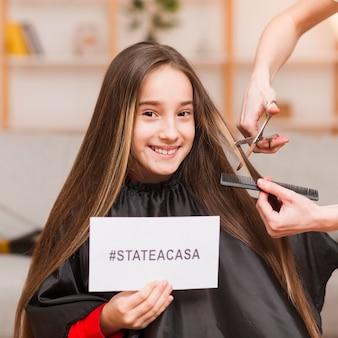Menina com corte de cabelo em casa