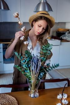 Menina com decoração de eucalipto e algodão-planta