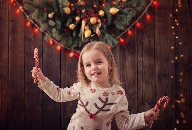 Menina com decorações de natal no fundo escuro de madeira
