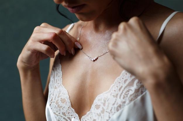 Menina com decote profundo com uma corrente de ouro em volta do pescoço