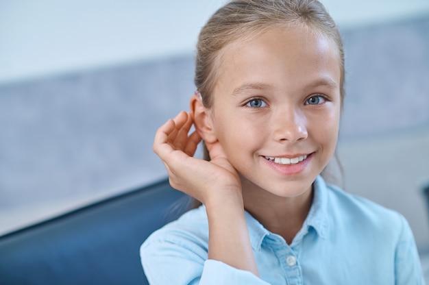 Menina com deficiência auditiva experimentando aparelho auditivo