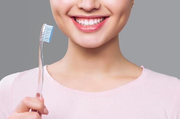 Menina com dentes brancos e saudáveis mantém uma escova de dentes e sorrisos. conceito de higiene bucal