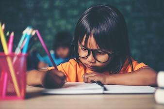 Menina com desenho a lápis na aula na sala de aula