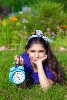 Menina com despertador no jardim de verão