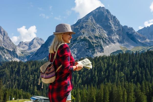 Menina com dinheiro nas montanhas