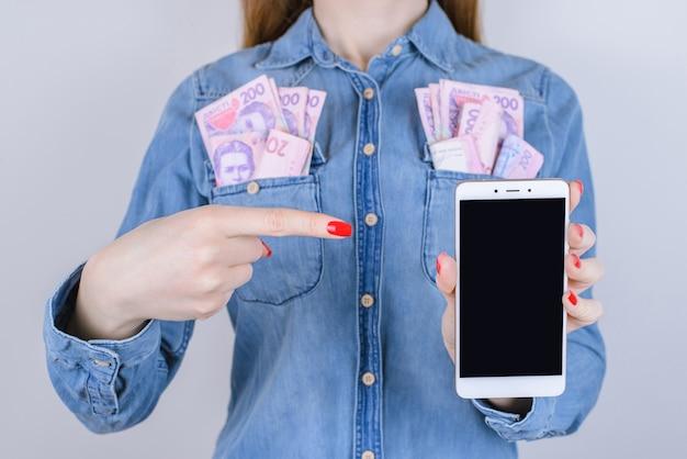 Menina com dinheiro no bolso aponta dedo no smartphone