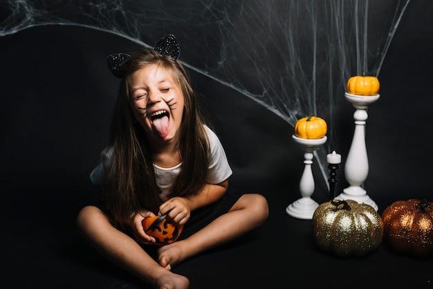 Menina com doces ou travessuras cesta perto de decorações de halloween