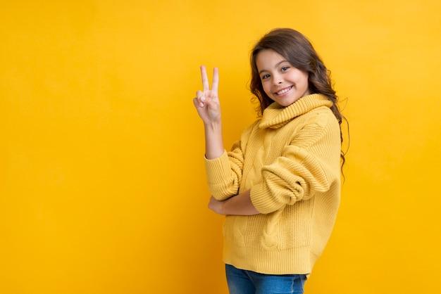 Menina com dois dedos levantados sorrindo