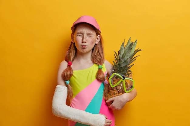 Menina com dois rabos de cavalo, rosto sardento, fecha os olhos e faz careta engraçada, se diverte nas férias de verão, usa maiô e boné, segura abacaxi com máscara de mergulho braço quebrado engessado