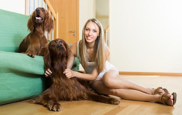 Menina com dois setters irlandeses em casa
