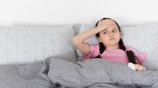 Menina com dor de cabeça, deitado na cama Foto gratuita