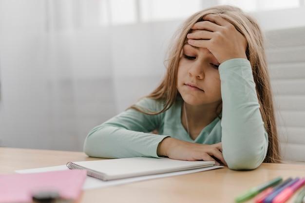 Menina com dor de cabeça enquanto dá aulas online