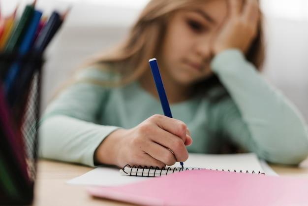 Menina com dor de cabeça enquanto faz o dever de casa Foto gratuita