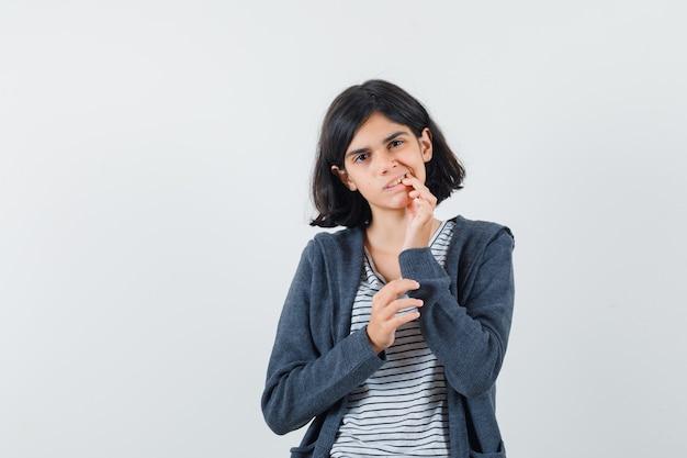Menina com dor de dente usando camiseta, jaqueta e parecendo desconfortável