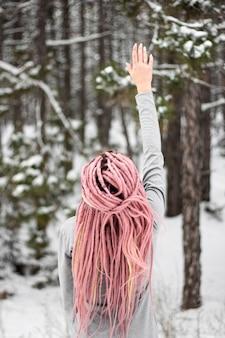 Menina com dreadlocks rosa na floresta no inverno