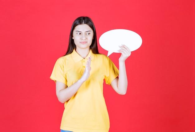 Menina com dresscode amarelo segurando um quadro oval de informações e parando alguém