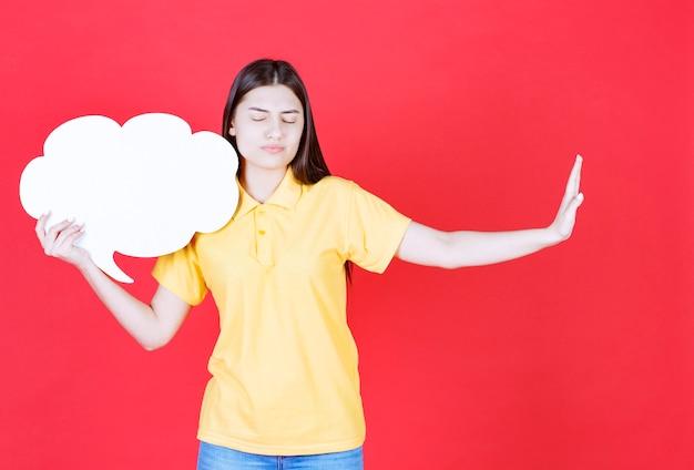 Menina com dresscode amarelo, segurando uma placa de informações de forma de nuvem e parando algo.