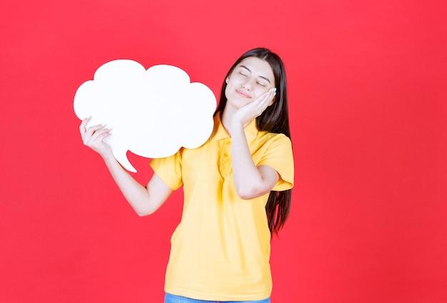 Menina com dresscode amarelo segurando uma placa de informações de forma de nuvem e parece cansada e com sono.