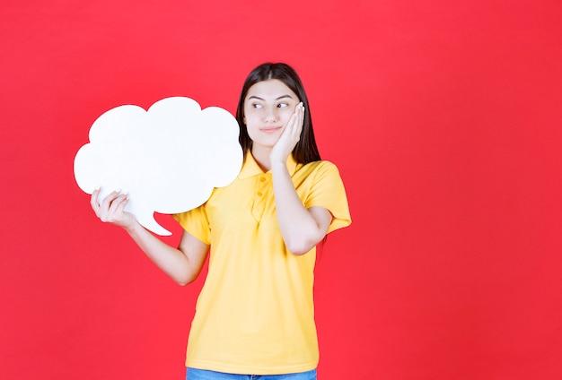 Menina com dresscode amarelo segurando uma placa de informações de forma de nuvem e parece confusa ou pensativa.