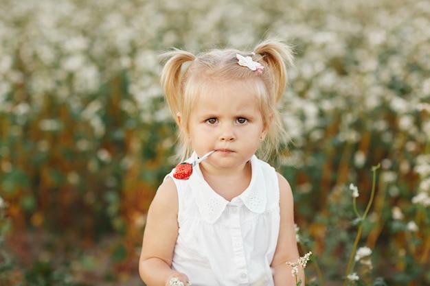 Menina com duas caudas. retrato de uma pequena menina carismática. menina com doces