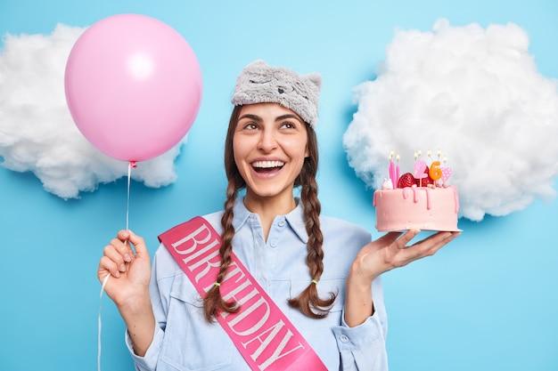 Menina com duas tranças concentradas acima tem expressão alegre segura bolo festivo e balão de hélio comemora 26 anos espera amigos na festa aceita parabéns