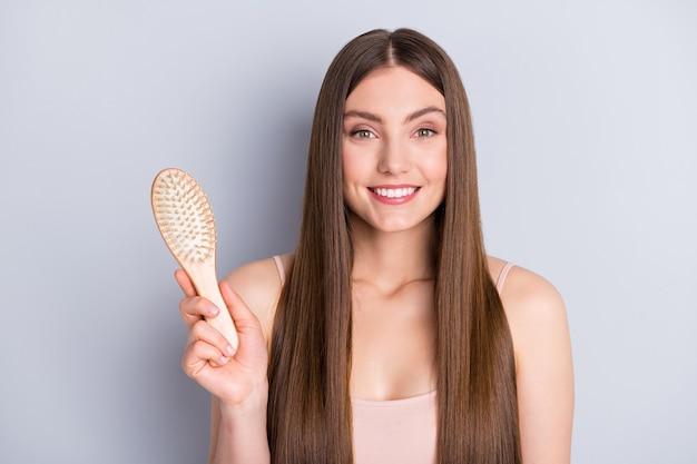 Menina com escova de cabelo na mão isolada em cinza