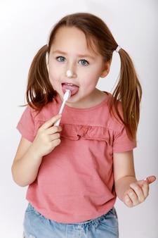 Menina com escova de dentes escovando os dentes degustando pasta de dente