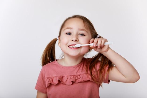 Menina com escova de dentes escovando os dentes