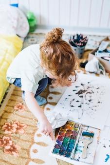 Menina com escova perto de conjunto de cores de água e papel sentado no chão