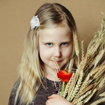 Menina com espigas de trigo e flores