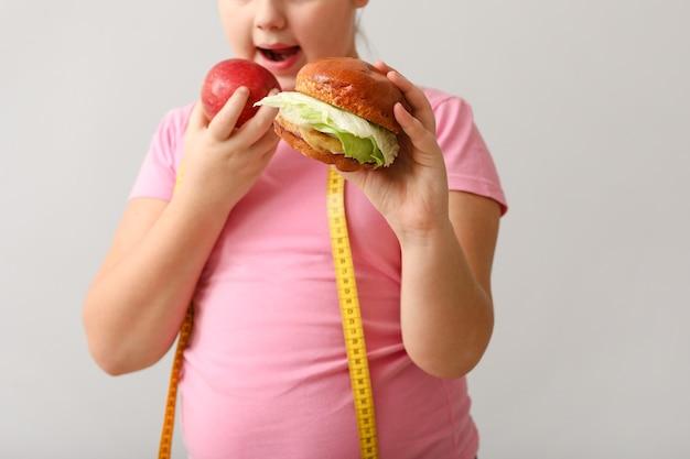 Menina com excesso de peso com comida saudável e não saudável